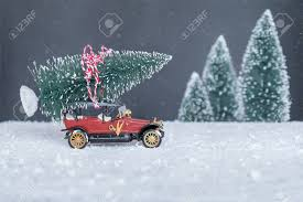 Small Retro Car With Christmas Tree On The Roof Going Holiday Stock Photo