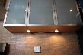 lighting cabinet puck lights with kitchen tile wall and