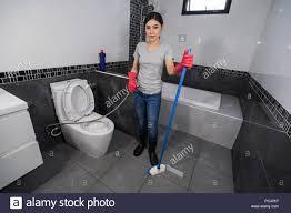 frau mit bürste für die reinigung der fliesen im badezimmer