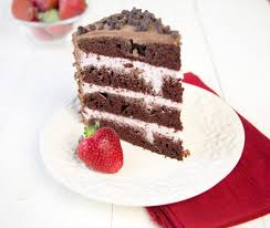 slice of 4 layer chocolate cake with strawberry mousse between the layers with chocolate frosting and