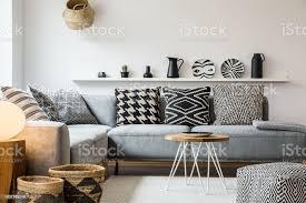 gemusterten kissen auf graue im modernen wohnzimmer interieur mit hocker und tisch aus holz echtes foto stockfoto und mehr bilder boho stil