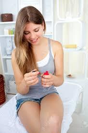 glühend junge frau lackieren ihre nägel mit roten lack im badezimmer