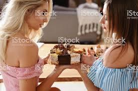 zwei schöne damen haben geburtstag oder hühnerparty beste freundinnen essen leckeren kuchen schwestern lachen fotos auf ihren smartphones machen und