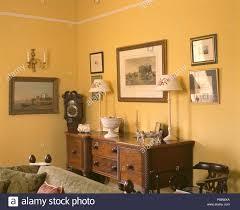 bilder an der wand oben sideboard in gelb wohnzimmer