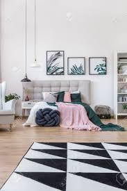 geometrischer teppich in rosa und grün schlafzimmer interieur mit len und beige fensterläden gegen eine wand mit floralen poster
