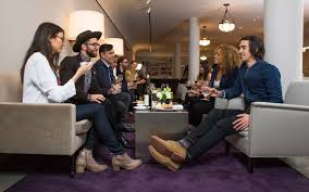 A Group Of Young Members Talk And Enjoy Drinks In An Elegant Lounge Space