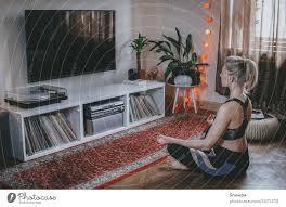 junge frau beim meditieren im wohnzimmer zu hause gesund