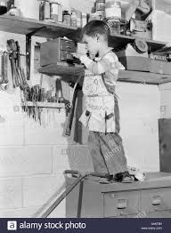 1950s 4 year old boy in garage tool shed standing on cabinet to