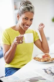 Une Femme Afro Américaine En Lisant Le Journal Femme Mûre Mangeant Le Petit Déjeuner Et Lisant Le Journal Photo