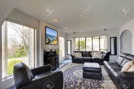 modernes wohnzimmer mit schwarzen möbeln und kamin