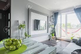 helles wohnzimmer mit weißem holztisch sofa großem fernseher und balkon