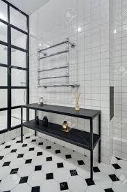 stilvolle badezimmer mit wänden aus weißen fliesen es ist dusche mit schwarzen trennwand aus glas quadrate schwarz gestell mit zubehör und verchromt