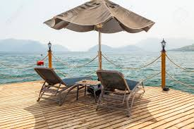 100 Wooden Parasols Pier With Sunbeds And Parasols On The Background Of Sea