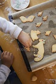 Cropped View Of Little Girl Decorating Baked Christmas Cookies With Sugar Pearls On Baking Tray One Person Elementary Age