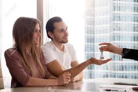 A Hand Of Female Real Estate Agent Giving Keys To Own First Apartment Couple