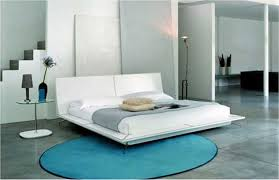 white floating bed added by blue rug on grey tile floor of