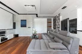 wohnzimmer mit grauem sofa und weißer offener küche