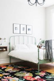 Feminine Yet Minimal Bedroom With A Floral Area Rug White Sconce And