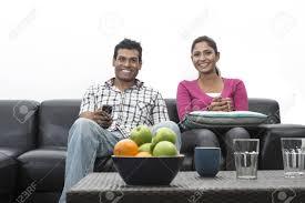 canape indien indien sur le canapé à regarder la télévision dans le