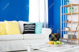 bunte kissen auf weißem sofa in blau und weiß lounge
