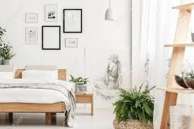 buchen sie gelegt auf einen hölzernen nachttisch mit anlage im grauen materiellen topf der im schlafzimmer mit poster auf der wand steht