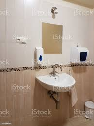 badezimmer interieur in hellen beige und weißen farben runde keramik waschbecken spiegel kunststoff seife teller und chrom armaturen zum händewaschen